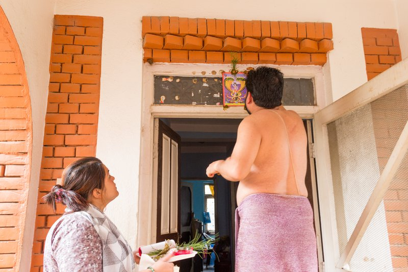 A Nepalese couple fixing a snake poster at their door.jpg