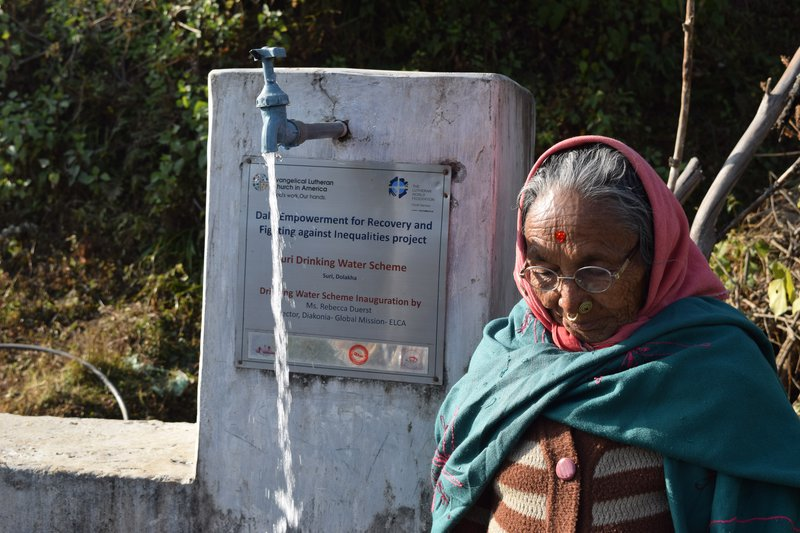 Ratna Maya BK of Suri village taking water from a tap constructed by LWF and ELCA.jpg