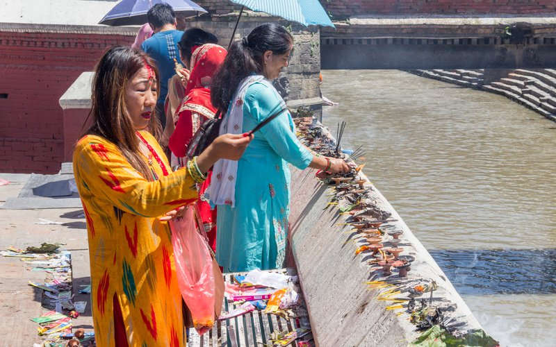 Women praying next to Pashupatinath temple duing Sharwan Monday festival.jpg